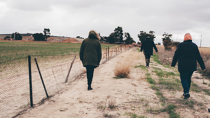 Staff walking along a path during an on country visit